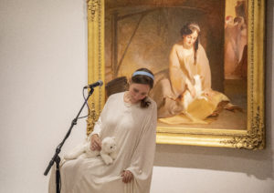 An actor with long, dark hair, pulled back by a headband, sits on a stool in front of a gold-framed painting. The actor wears a white gown and is holding a stuffed cat. The actor's outfit and pose mirrors what is depicted in the painting. There is a microphone on a stand in front of the actor.